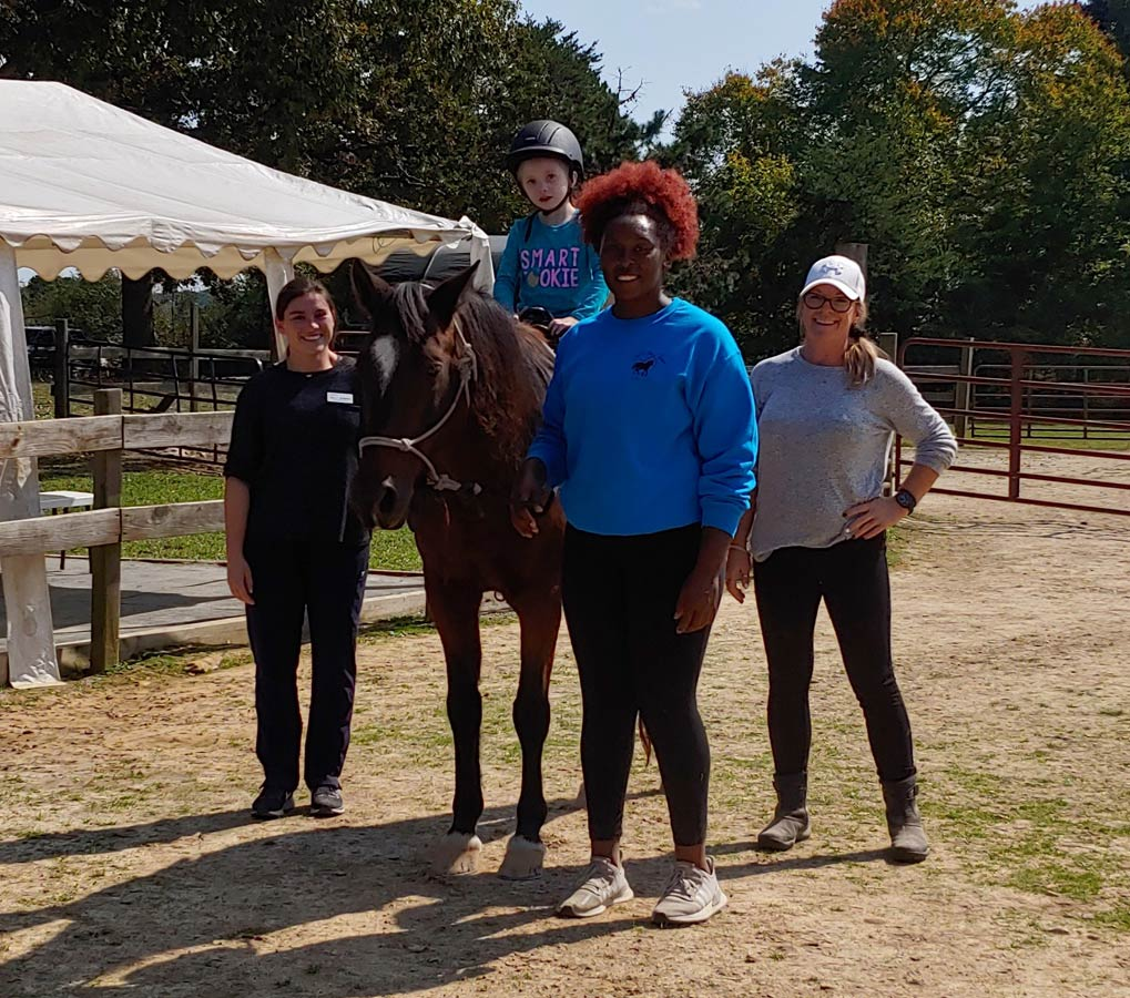 Another therapy rider with instructor, therapist and therapist assistant